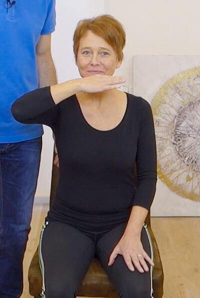 Die Person zeigt eine Übung gegen Kieferschmerzen