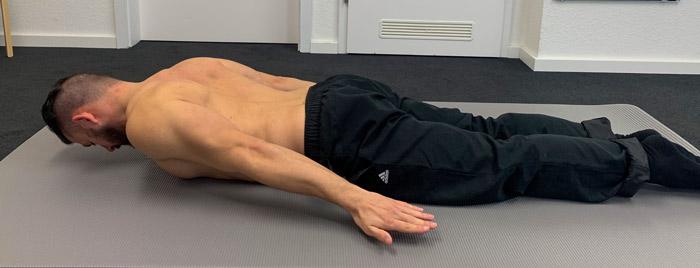 Das ist ein Bild, das eine Stabilisationsübung in Bauchlage für den Rücken veranschaulicht.
